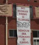 ACLU poster No Human is Illegal EnglishSpanish outside of bldg