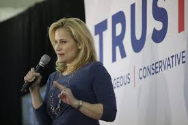 Heidi speaking in front of TRUSTED sign